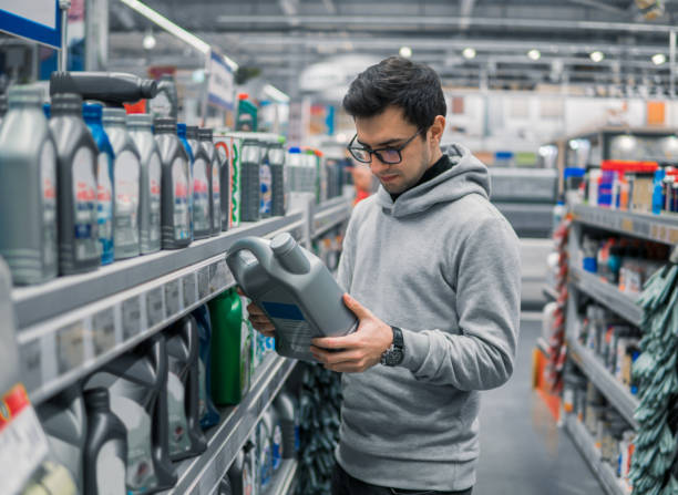male customer buying engine lubricating oil in the car supermarket male customer buying engine lubricating oil in the car supermarket. Difficult decision which motor oil to buy vehicle part stock pictures, royalty-free photos & images