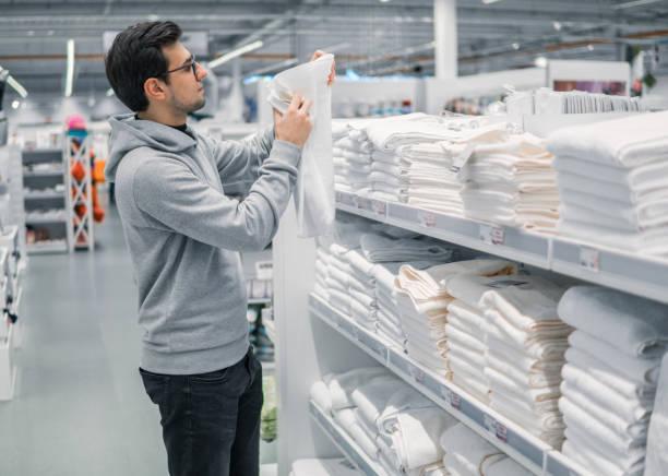 männlichen kunden prüfen und handtücher im supermarkt zu kaufen - stoffregal stock-fotos und bilder