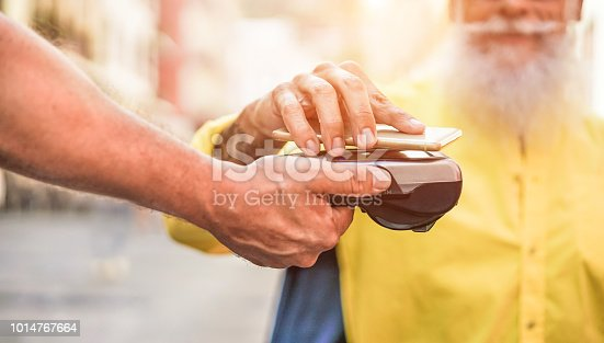 istock Male customer paying with contactless smartphone with web app - Waiter with a credit card reader machine at bar outdoor - New tech payment concept - Focus on top hand 1014767664