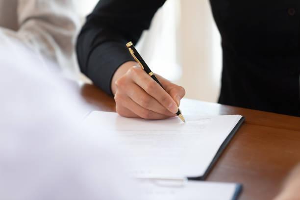 mannelijke klant ondertekenen bedrijfsdocument op tabel, close-up weergeven - notaris stockfoto's en -beelden