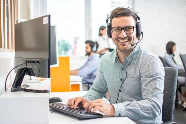 Male customer support phone operator with headset working in call centre. Group of sales agent working in office. stock photo