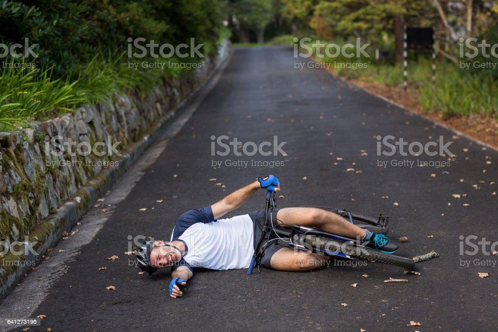 Cycliste masculin tombé de son vélo de montagne sur la route - Photo