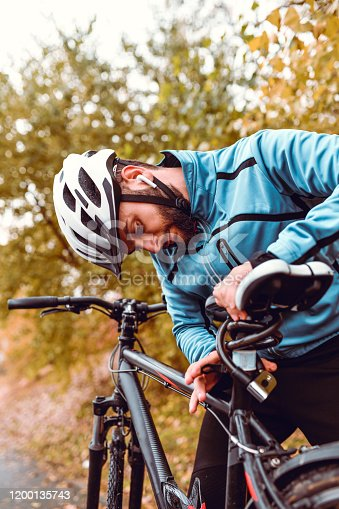 istock Male Cyclist Locking Bicycle Seat 1200135743