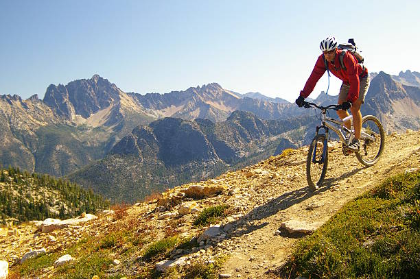 male cyclist riding mountain bike high mountains - mountain bike stock pictures, royalty-free photos & images