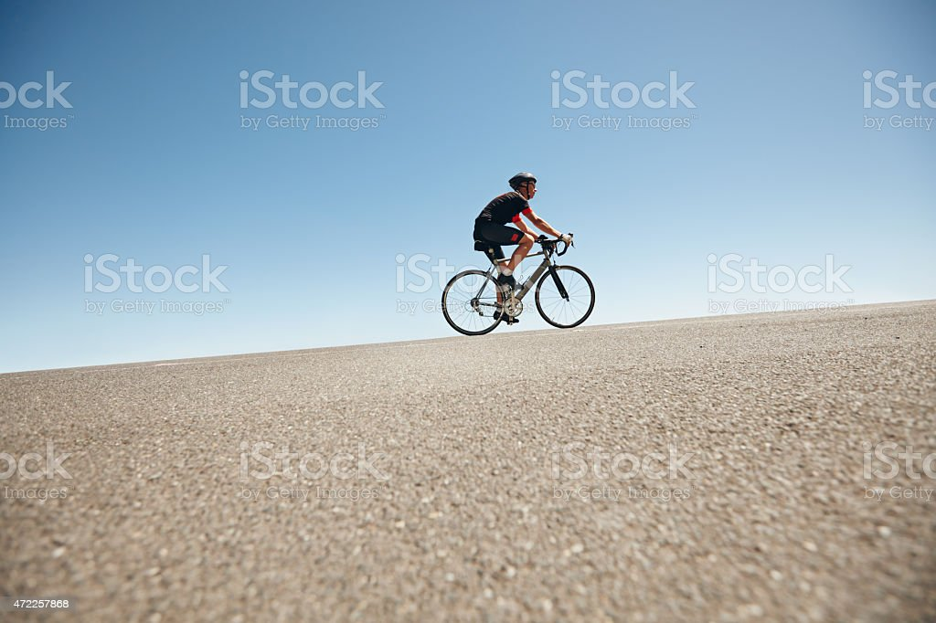 Male cyclist riding on a flat road against blue sky stock photo