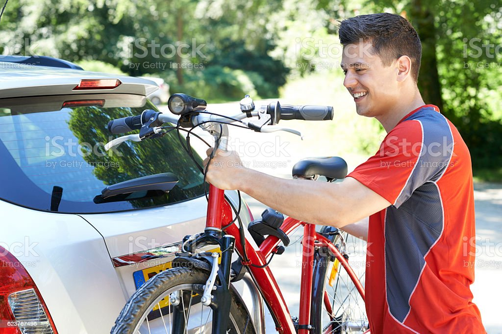 Male Cyclist Taking Mountain Bike From Rack On Car stock photo