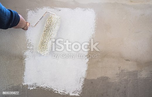 835790922istockphoto Male decorator painting wall with paintbrush 865035622