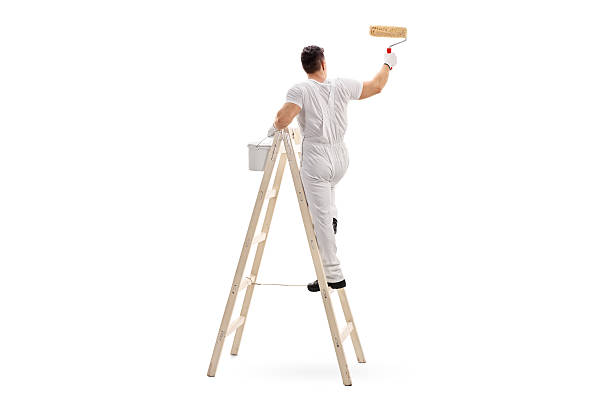 male decorator painting with a roller - painter stock photos and pictures