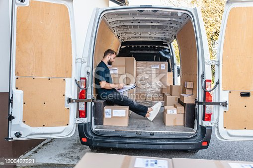 Rear doors open on delivery van and young independent delivery driver taking stock of parcels onboard for transport.