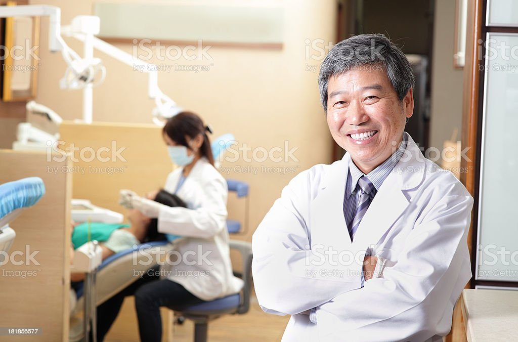 male dentist and team in his dental office stock photo