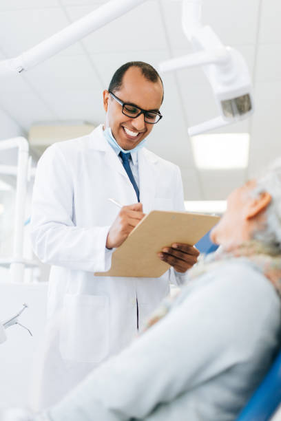 Male dentist consulting senior patient and smiling stock photo