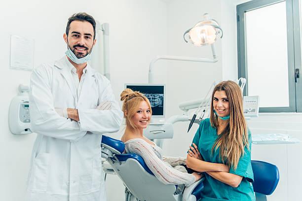 Männliche Zahnarzt, seine Assistenten und weibliche Patienten in dental practic – Foto