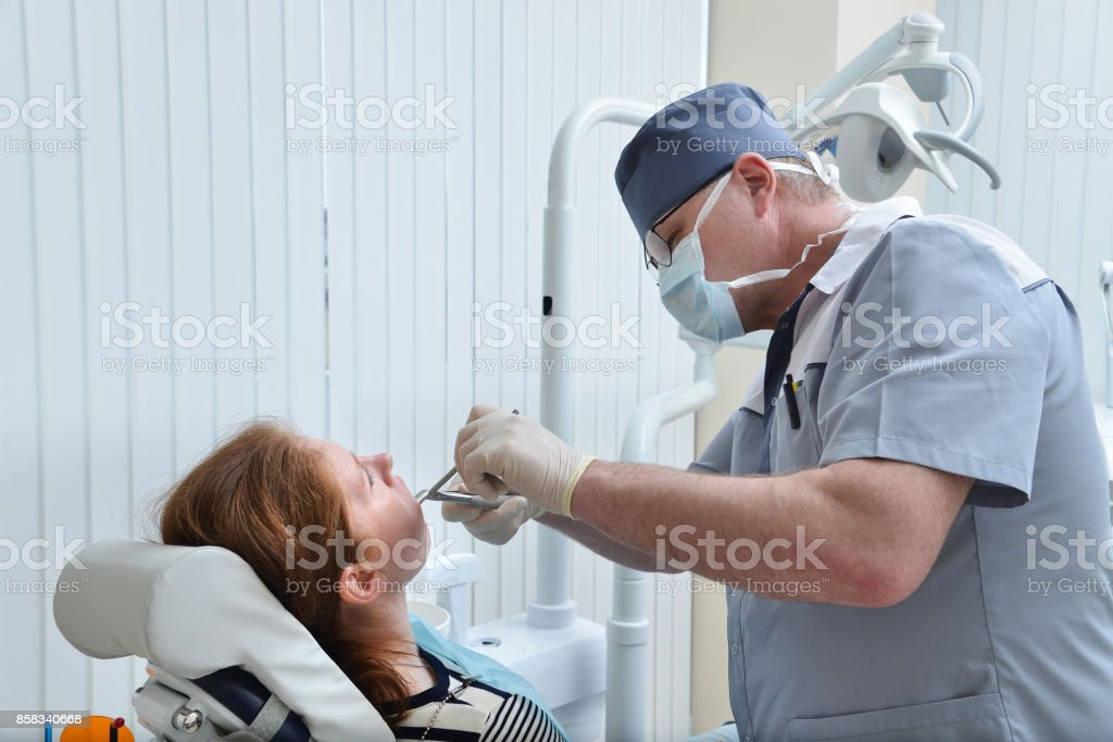 Male Dentist remove tooth of woman patient using forceps. Health care dentistry medicine concept. stock photo