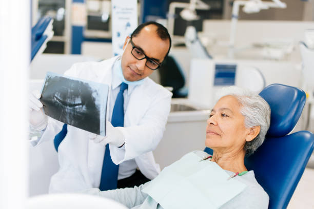 Male dentist showing x-ray to senior patient stock photo