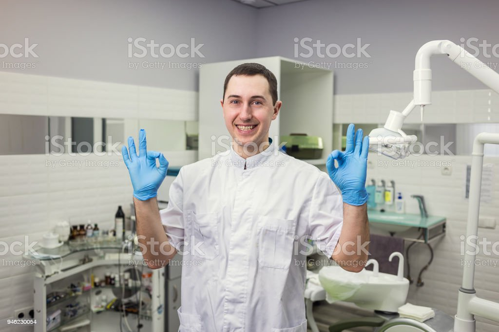 Male dentist standing over medical office background. Healthcare, profession, stomatology and medicine concept stock photo
