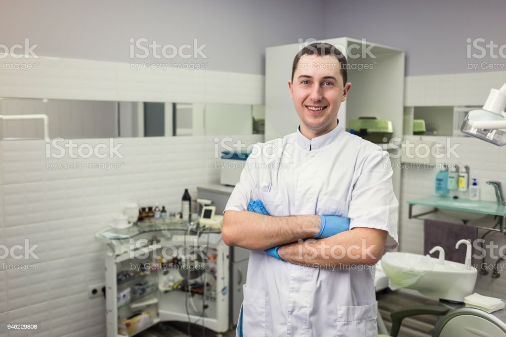 Male dentist standing with his hands crossed over medical office background. Healthcare, profession, stomatology and medicine concept stock photo