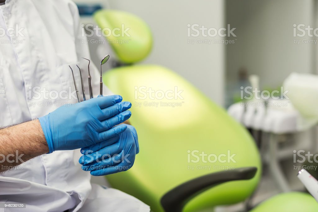 Male dentist with tools over medical office background. Healthcare, profession, stomatology and medicine concept stock photo