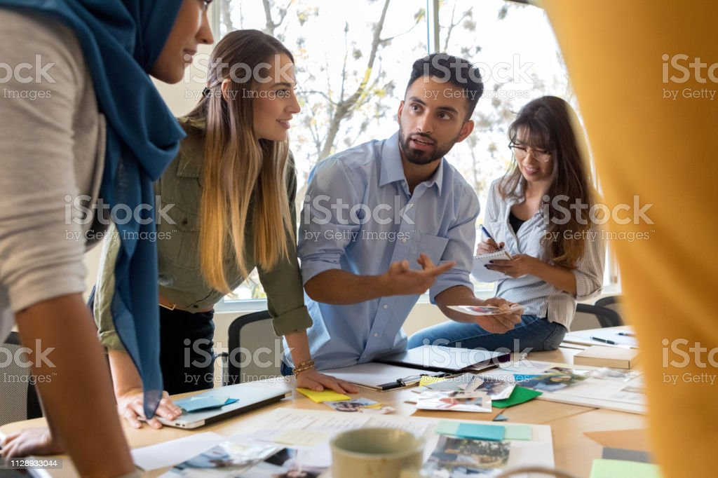 A serious male design professional stands with his team around a...
