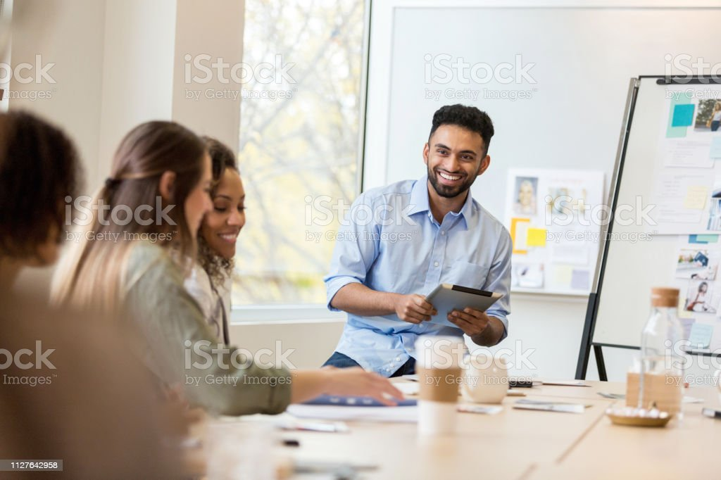 A cheerful male design professional sits in a conference room and...