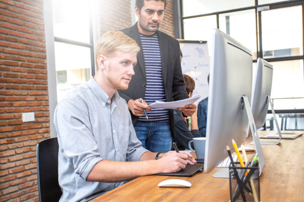 Male designer working at modern office with team. Manager comes to brief to designer for project. stock photo