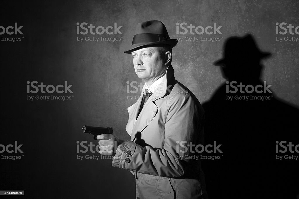 male detective with a gun in 40s film noir style royalty-free stock photo