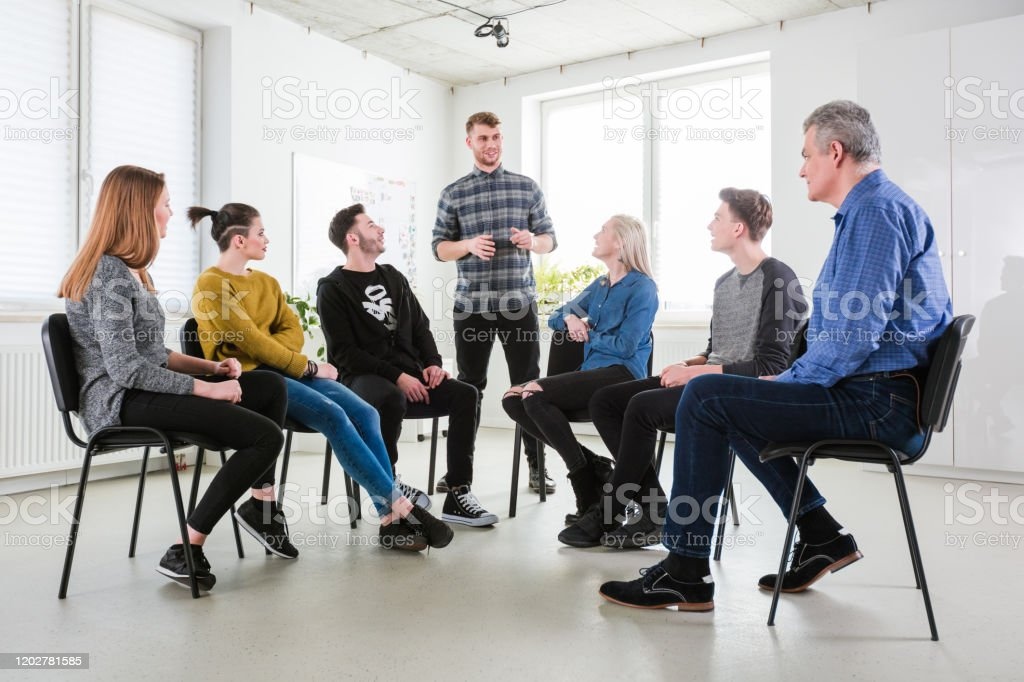 Male discussing views with friends and therapist Smiling young male student discussing his views with friends and therapist. Men and women are having meeting in lecture hall. They are solving problems. 18-19 Years Stock Photo