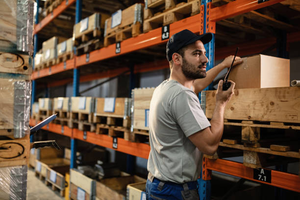 mannelijke verzender communiceren over walkie-talkie tijdens het werken in een magazijn. - warehouse worker stockfoto's en -beelden