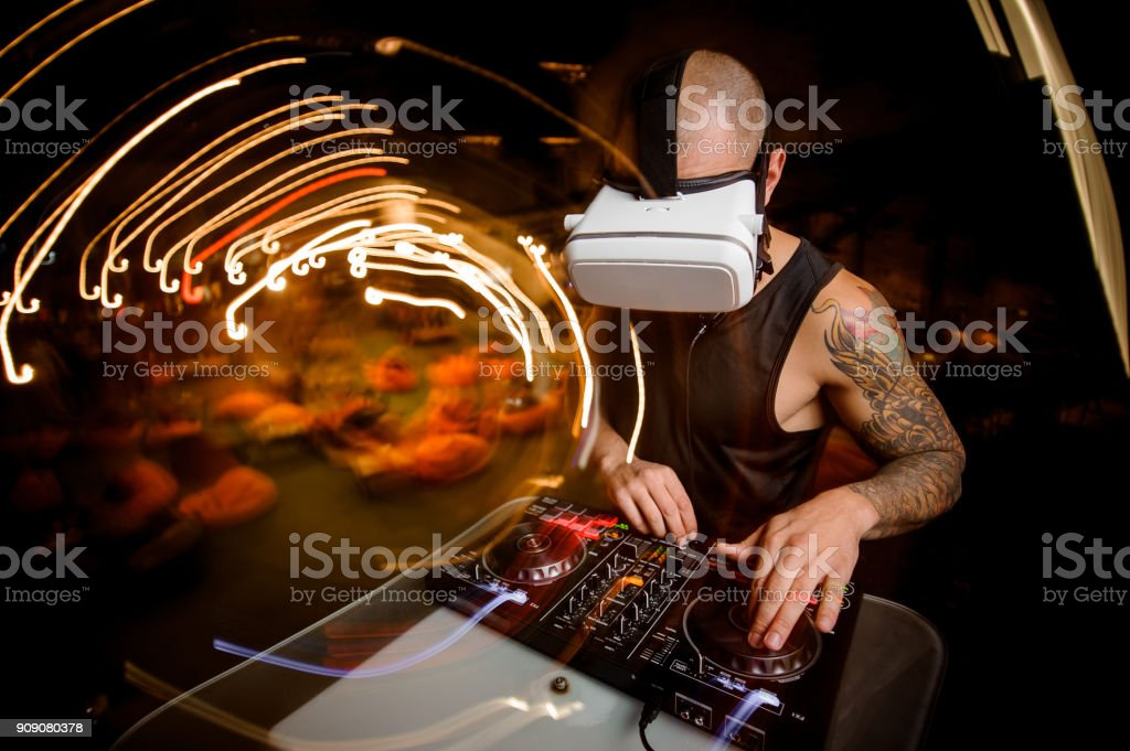 Male DJ in glasses of virtual reality in the process of work stock photo