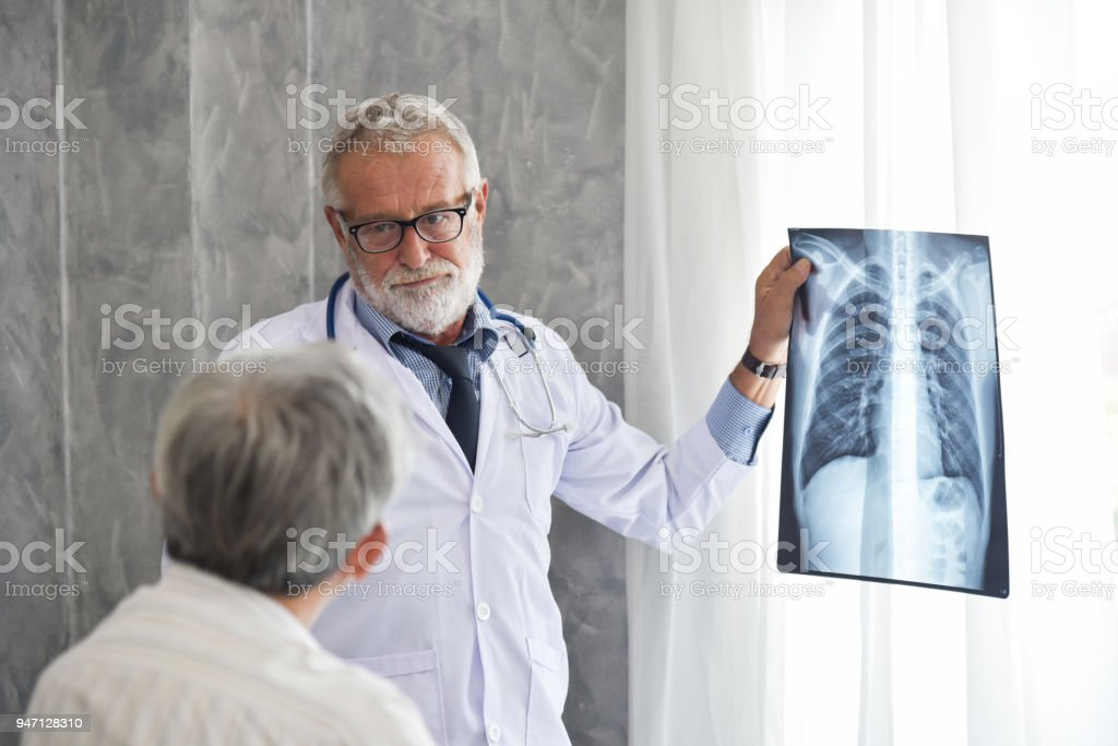 Senior Male doctor and Asian patient are examining x-ray film in a...