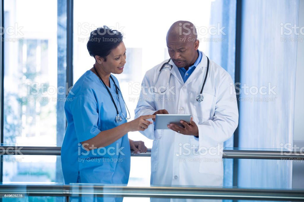 Male doctor and nurse using digital tablet in corridor Male doctor and nurse using digital tablet in corridor at hospital 30-39 Years Stock Photo