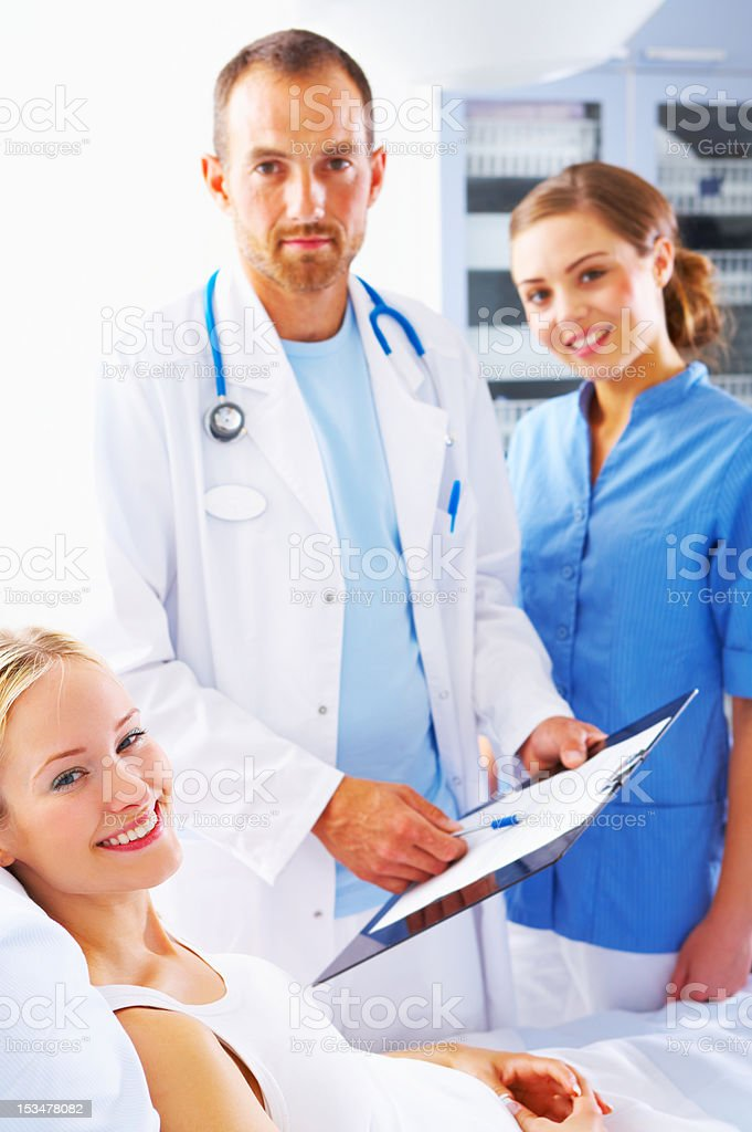 Male doctor and nurse with a female patient Male doctor and nurse with a female patient. Accidents and Disasters Stock Photo