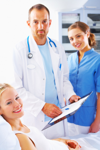 Male Doctor And Nurse With A Female Patient Stock Photo - Download Image Now