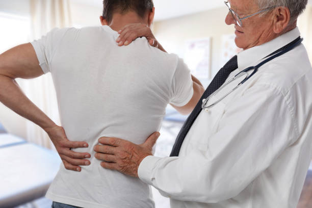 Male Doctor and patient suffering from back pain during medical exam. stock photo