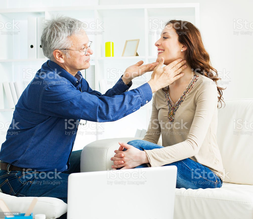 Male Doctor Checking Female Patient Glands stock photo