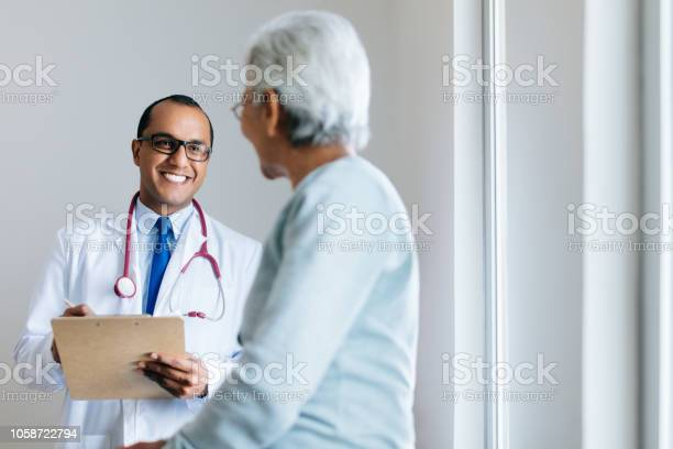 Male Doctor Checking Senior Female Patient And Smiling Stock Photo - Download Image Now