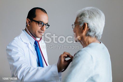 A latin male doctor checking female senior's heart with stethoscope, listening and looking away.