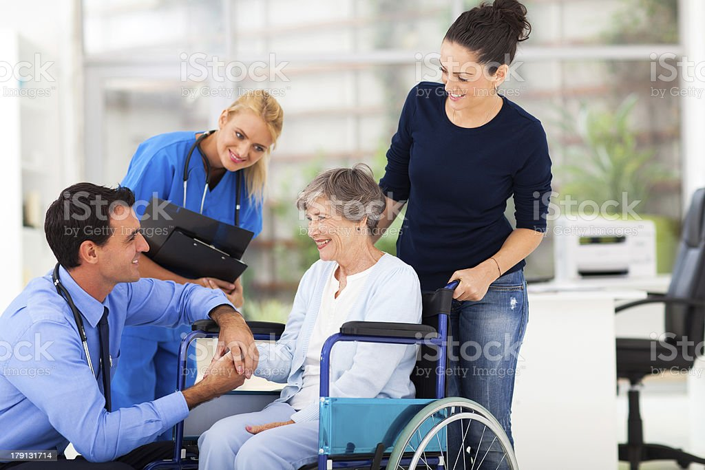 male doctor comforting senior patient stock photo