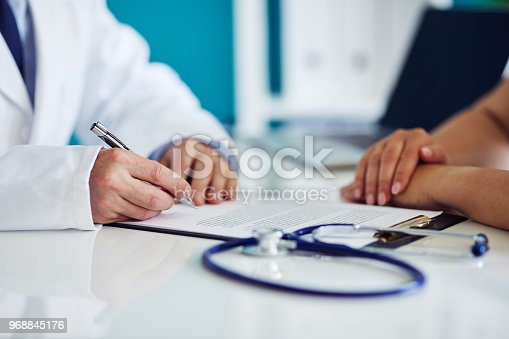 istock Male doctor consults with his patient and writes notes on the clipboard 968845176