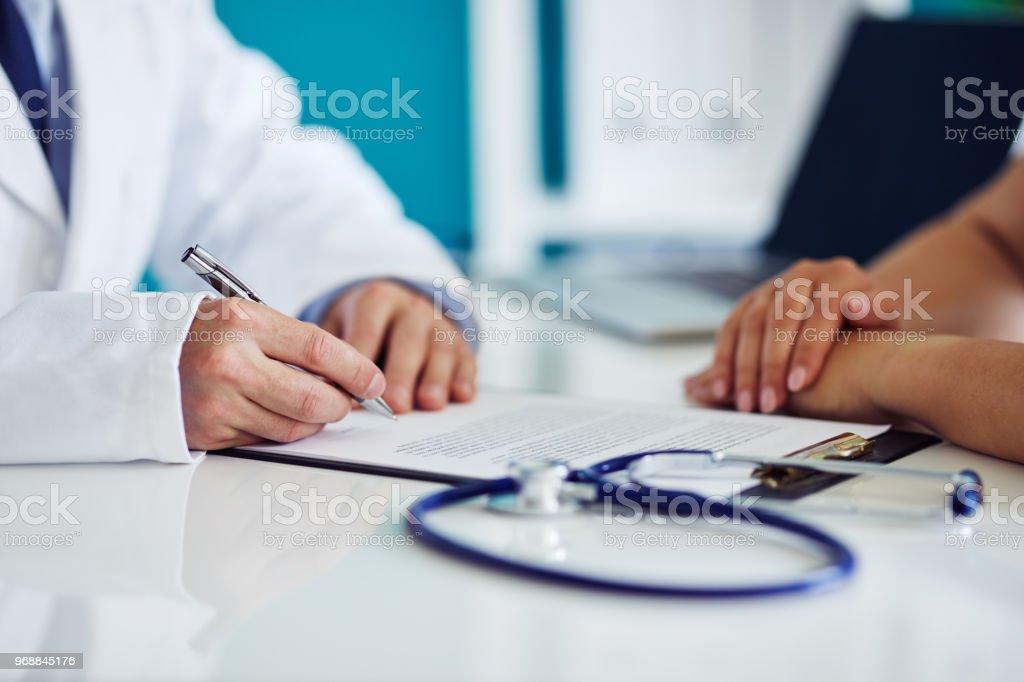 Männlichen Arzt berät sich mit seinem Patienten und schreibt Notizen über die Zwischenablage – Foto