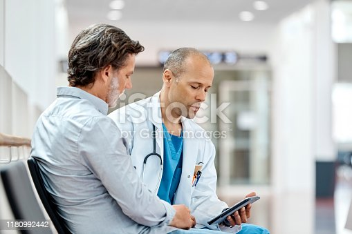 Male doctor using digital tablet while counseling mature patient in waiting room. Mature is discussing with medical professional in hospital. They are sitting on seat.