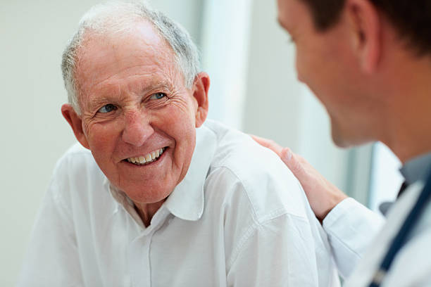 Male doctor discussing with his patient Male doctor discussing with his patient 65 69 years stock pictures, royalty-free photos & images