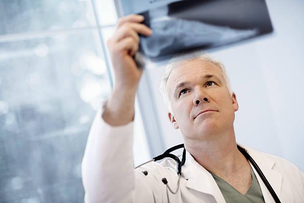 Männlichen Arzt untersuchen ein Röntgenbild – Foto