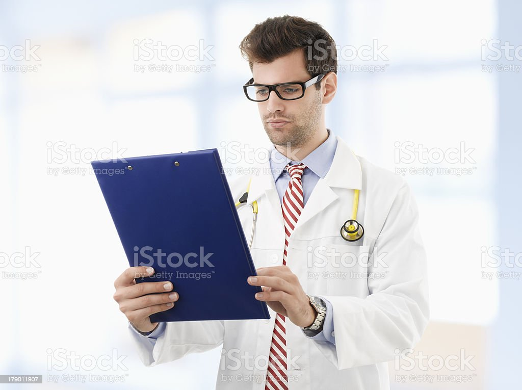 Male doctor examining medical report royalty-free stock photo