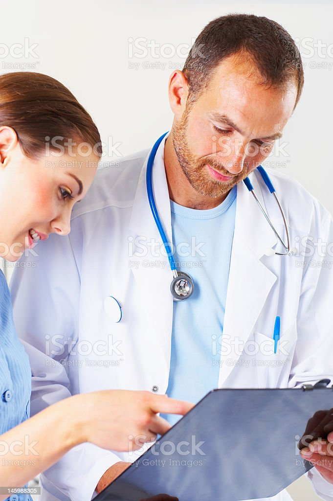 Male doctor examining medical report with a female nurse royalty-free stock photo