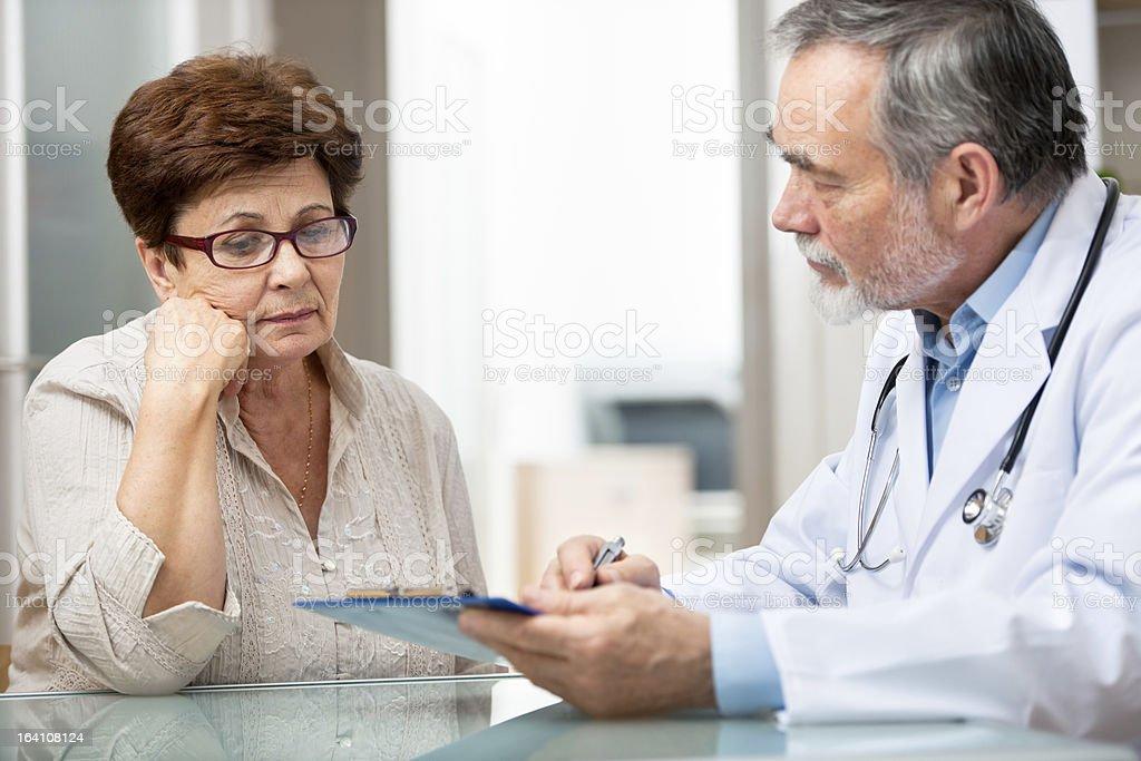 Male doctor explaining something to female patient stock photo