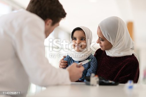 A male doctor explains how to inject insulin to a young Muslim girl as she sits on her mom's knee.