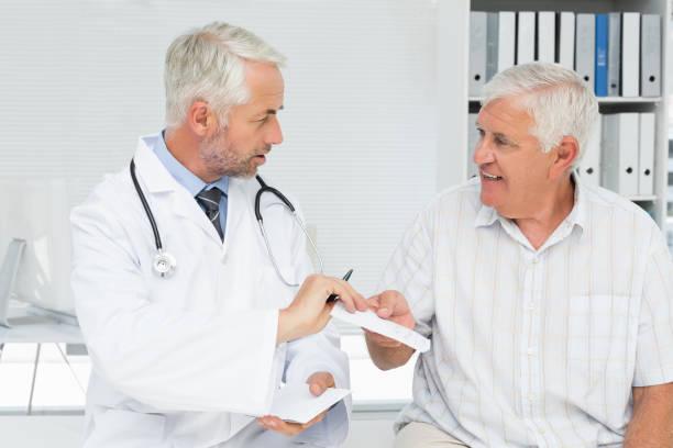 männlichen arzt ein rezept zu seinem älteren patienten geben - südafrikanische rezepte stock-fotos und bilder