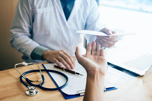 Male Doctor Handing A Prescription To The Patient - Fotografie stock e altre immagini di Accudire