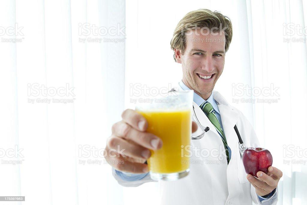 Male doctor holding apple and orange juice royalty-free stock photo