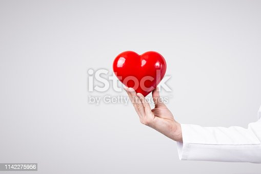 1035479448 istock photo Male doctor holding heart in his arms. Healthcare and cardiology concept in medicine 1142275956